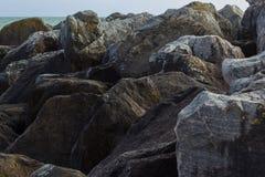 Flusssteine in Saltdean, Brighton im Meer Stockbilder