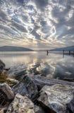 Flusssteine, See und bewölkter Himmel Stockbilder