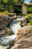Flussstrom mit Felsen und Brücke Stockfotos