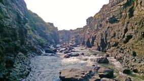 Flussstrom zwischen Hügeln in einer Gebirgsregion stockbild
