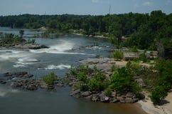 Flussstromschnellen in der Bewegung mit Holz und im Grün um es lizenzfreies stockfoto