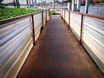 Flussufer-Ansicht von Diamond Checkered Plate Walkway zum Pier Stockfotos