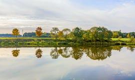 Flussuferszene mit Bäumen, die im Fluss Tauber reflektiert werden Lizenzfreie Stockfotos