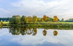 Flussuferszene mit Bäumen, die im Fluss Tauber reflektiert werden Stockbild