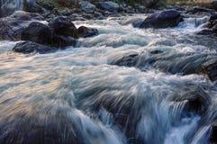 Flusswasser, das Felsen an der Dämmerung durchfließt Lizenzfreie Stockfotografie