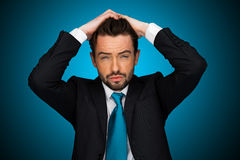 Flustraded businessman on blue background , Royalty Free Stock Photo