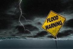 Flut-Warnzeichen versenkt in steigendes Wasser mit st?rmischem Hintergrund lizenzfreie stockbilder