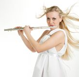 Flute. A girl with freckles playing on flute Royalty Free Stock Photo