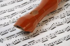 Flute. In wood on white  music sheet Royalty Free Stock Photo