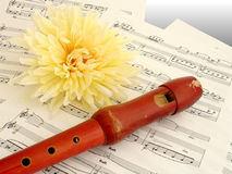 Flute. On music sheets with a yellow flower Stock Images