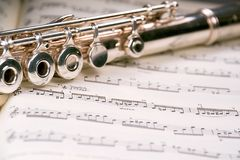 Flute across a musical score. A used flute rests across an open musical score. Only one line of music is in focus Royalty Free Stock Images