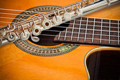 The Flute and a classical guitar. A 14k rose gold flute place on a cutaway classical guitar Stock Photo