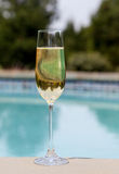 Flute of cold champagne by side of pool Royalty Free Stock Photos