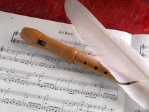 Flute and Feather. Wooden classic flute and white feather over a music partiture Stock Photos
