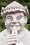 Flute Fingering. Concrete statue of a minstral playing an old fashioned wooden flute stock photo