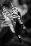 Flute in the hands of a musician in the orchestra closeup Royalty Free Stock Image