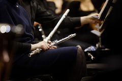 Flute in the hands of a woman in an orchestra. In dark tones Royalty Free Stock Image