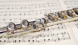 Flute Keys. Closeup view of the keys of a metal flute, shot on a music sheet Royalty Free Stock Image