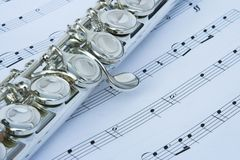 Flute keys on music notes. Silver flute on a background of music notes. Image is of some of the keys on the instrument. Flute is placed at a diagonal on the stock photos
