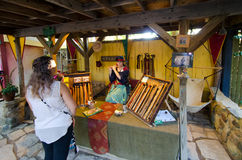 Flute Maker. A craftswoman demonstrates one of her creations for a customer in the marketplace at the Bristol Renaissance Faire in Wisconsin Stock Photos