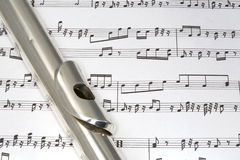 Flute mouthpiece on Sheet music. Macro shot of Flute on sheet music Royalty Free Stock Photos