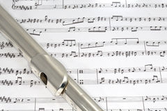Flute mouthpiece on Sheet music. Macro shot of Flute on sheet music Royalty Free Stock Image