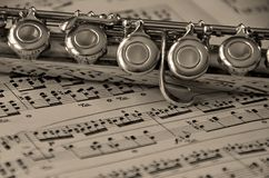 Flute on Music. Sepia toned flute instrument laying on music Royalty Free Stock Images