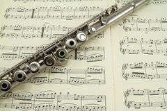 Flute on a Music Book. A silver flute resting on a music book Stock Photography