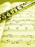 Flute music instrument and score. A still life image of a flute musical instrument laid across a page of music score.  Vertical image, processed to golden yellow Royalty Free Stock Photography