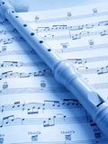 Flute and music score. Recorder woodwind musical instrument and page of music score in blue Stock Photography