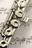 Flute on music sheet. Well worn student flute sits on a sheet of music Royalty Free Stock Photography
