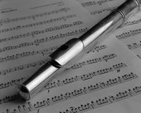 Flute and Music. Still life of silver flute resting on sheet music; large format black and white film Royalty Free Stock Images