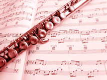 Flute musical instrument & score. A still life image of a flute music instrument laid across a page of classical music score.  Vertical image, processed to Royalty Free Stock Images