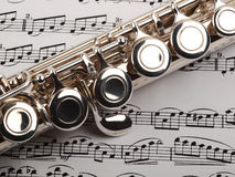 Flute and musical notes. A used flute rests across an open musical score. Only one line of music is in focus Royalty Free Stock Images