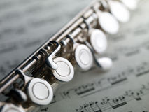 Flute on musical score Stock Photos