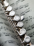 Flute on musical score. Close up photo of a flute on musical score Royalty Free Stock Image