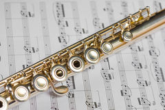 Flute on a musical score Stock Photos