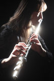 Flute musician flutist. Flute playing flutist musician performer with bright musical instrument on the black background Royalty Free Stock Photo