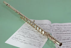 Flute and notes. Are on a colored background Stock Photos