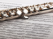 Flute and notes. A used flute rests across an open etude musical score Stock Photos