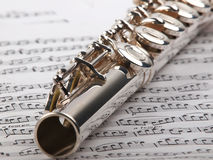 Flute and notes. A used flute rests across an open musical score. Only one line of music is in focus Royalty Free Stock Images