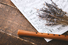 Flute with notes and lavender on the wooden table Stock Images