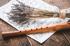 Flute with notes and lavender on the wooden table horizontal. Flute with notes and lavender on the old wooden table horizontal Royalty Free Stock Images