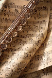 Flute on old handwritten folded sheet music top view vertical. Flute on old handwritten folded sheet music. Vertical composition. Top view Royalty Free Stock Photos