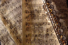 Flute on old handwritten sheet music top view horizontal composi Royalty Free Stock Images