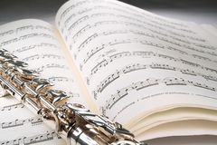 Flute on an open musical score with gray background. A flute lies transversely across on an open musical score against a grey background. The musica fades off Stock Photo