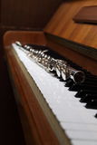 Flute and piano. Flute laying on an old piano keyboard Royalty Free Stock Photography