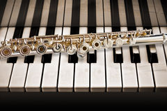 The Flute On The Piano. A solid silver flute placed on the piano keys Royalty Free Stock Image