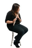 Flute Player. A teenage girl is sitting on a stool while playing the flute, isolated against a white background Stock Photography