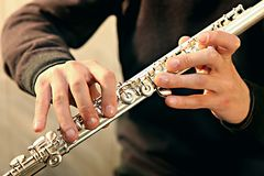 Flute player's hands. Hands of a flute player and a flute itself Stock Photography